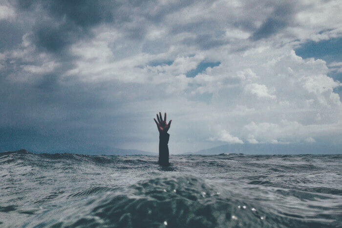 Hand reaches out of water while sinking, cognitive hypnotherapy can help relieve stress