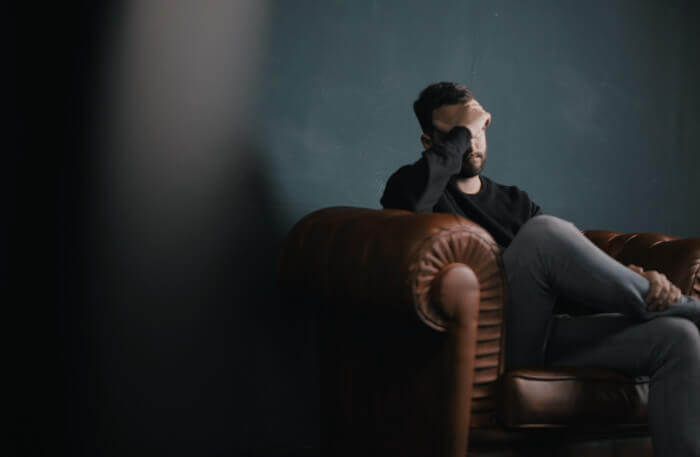 Depressed man sits with head in hands in therapy session - cognitive hypnotherapy for depression
